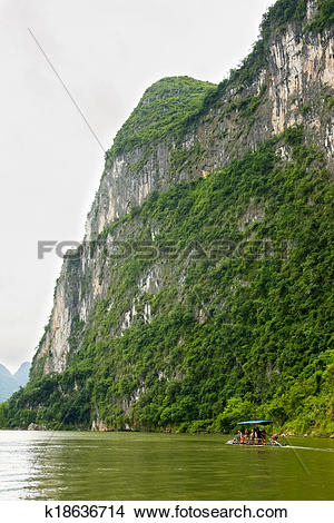 Stock Photo of Big limestone cliff and bamboo boat k18636714.