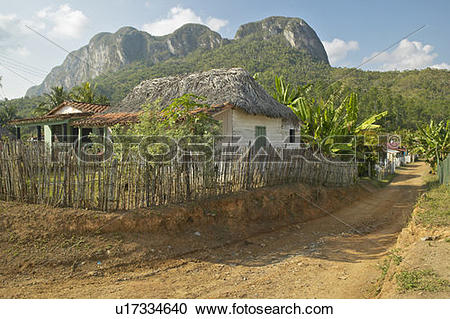 Stock Photography of Small houses in front of limestone mountains.