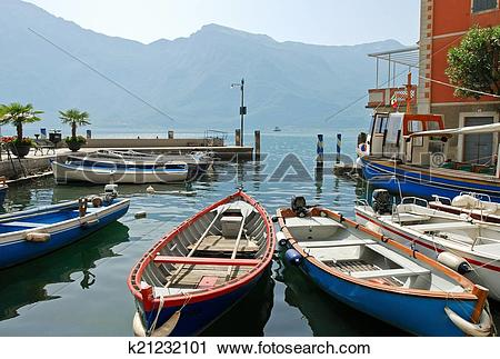 Stock Photography of boats near pier in town limone sul garda.