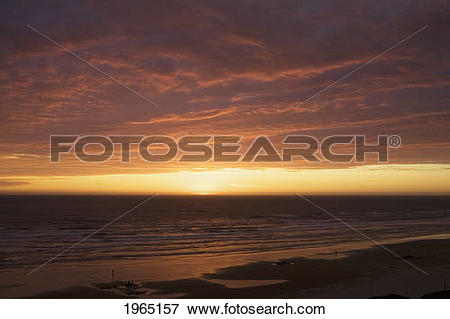 Picture of dramatic clouds at sunset on a beach with the light.