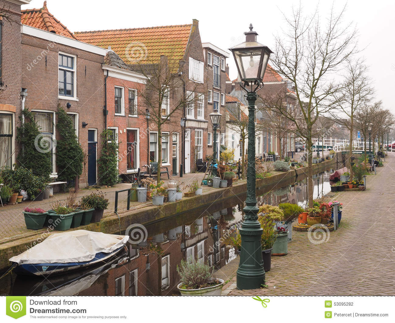 Small Tree Lined Canal Amidst Residential Housing In Holland.