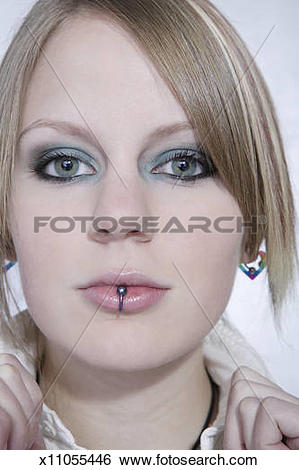 Stock Images of Young woman with lip ring adjusting collar.