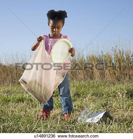 Stock Images of Young girl picking up litter u14891236.