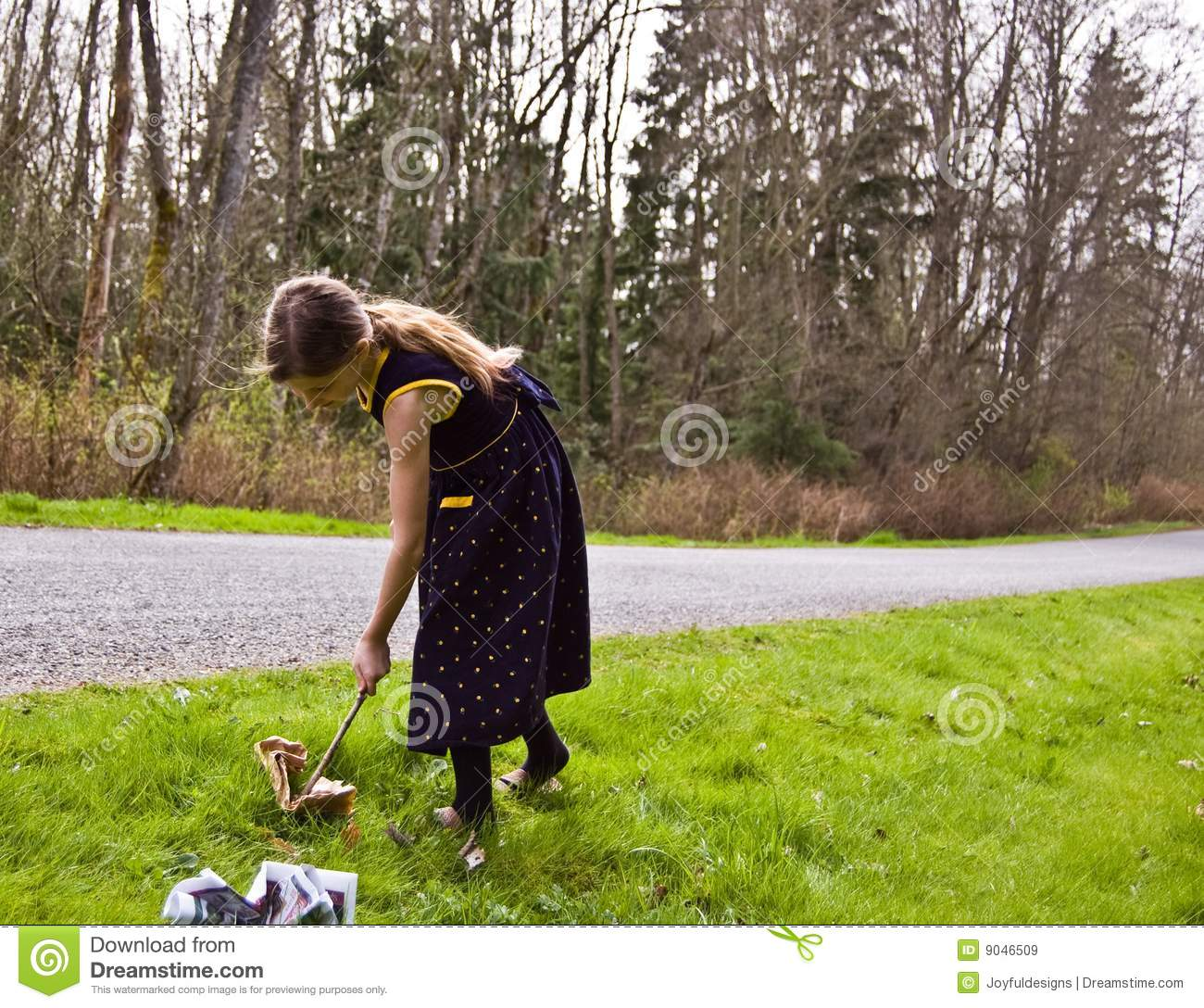 Young Girl Picking Up Litter With A Stick Royalty Free Stock.