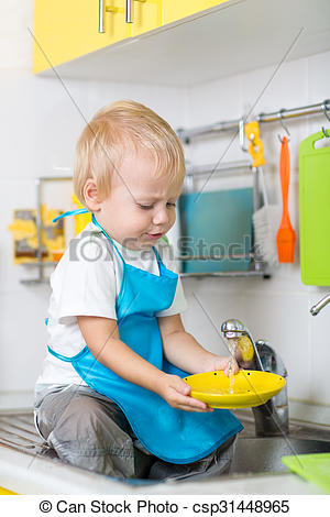 Stock Image of funny little boy sitting on kitchen table and.