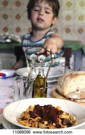 Stock Images of A little boy sitting at a table pointing to a.