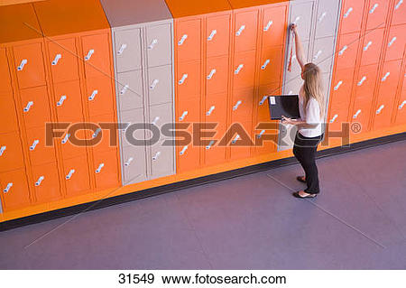 Stock Photograph of Girl opening locker in school corridor 31549.