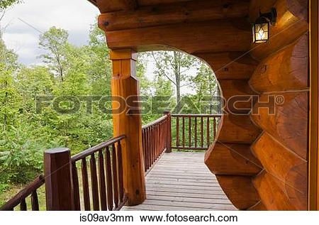 Stock Photo of Exterior of cottage style log home with arch and.