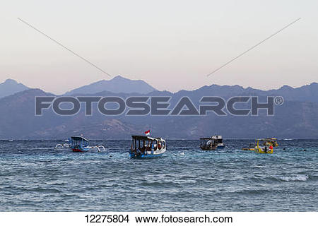 Stock Photo of Boats in the Lombok Strait with Lombok island in.