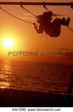 Stock Photography of child on a swing, at sunset, at a beach.
