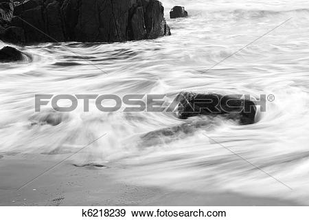 Stock Photograph of Wave withdrawing making patterns with slow.