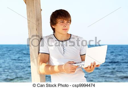 Stock Photo of Young man with laptop look away at beach csp9994474.