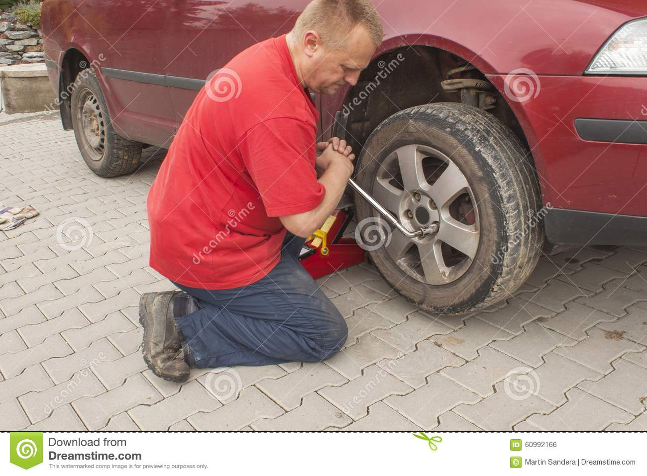 Man Changing The Punctured Tyre On His Car Loosening The Nuts With.