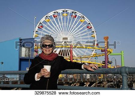 Pictures of Woman holding a drink in an amusement park, Santa.