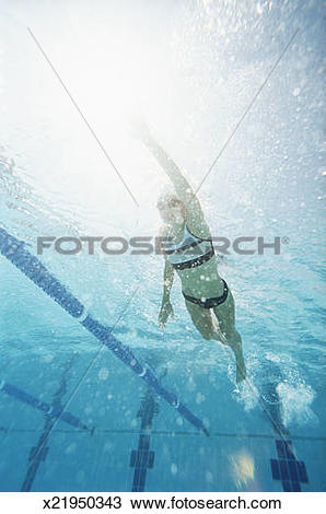 Stock Photo of Low Angle Shot of a Young Woman Swimming in a Pool.