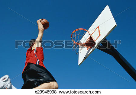 Pictures of low angle shot of a man slam dunking a basketball.