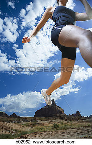 Stock Photo of Low angle shot of a woman running in the desert.