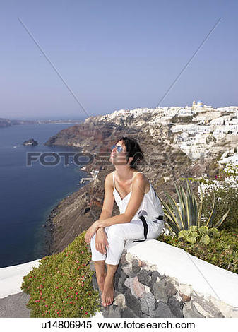 Stock Image of Woman sitting on a low wall u14806945.