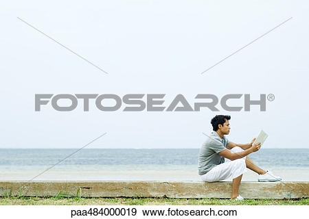 Stock Photograph of Man sitting on low wall at the beach, reading.