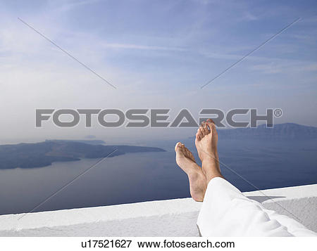 Picture of Men's feet on a low wall, sea view u17521627.