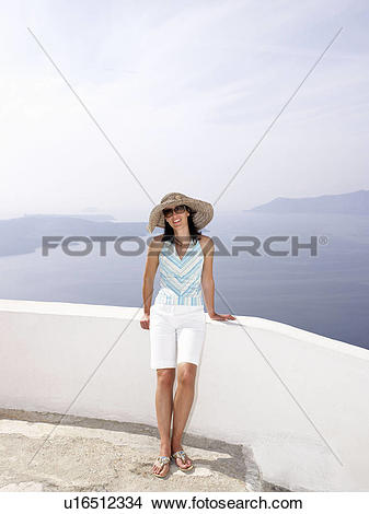 Stock Photo of Woman leaning on a low wall, sea view u16512334.