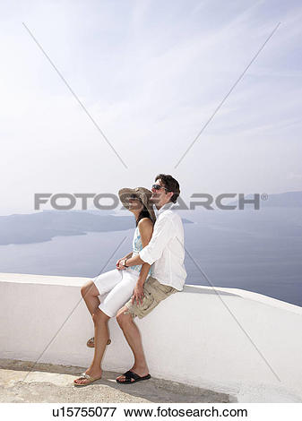 Picture of Couple leaning on a low wall, sea view u15755077.