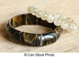 Stock Photos of lucky stone bracelets on wood background, closeup.
