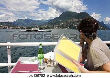 Stock Photo of Woman reading menu in restaurant overlooking rural.