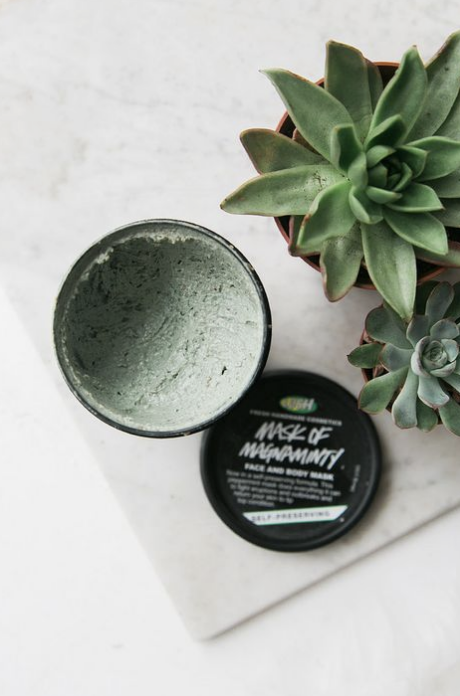 Lush green mask, styled flatlay on white marble with.
