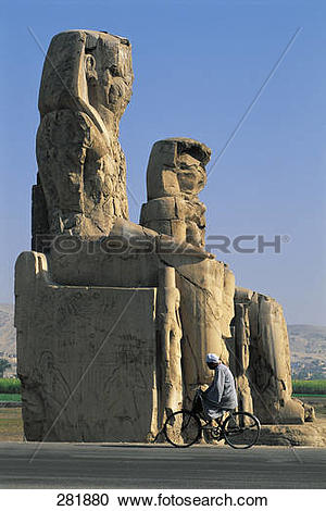 Stock Photography of Man cycling beside Egyptian sculptures.