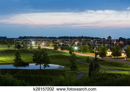 Stock Photo of Luxury Neighborhood Bordering Golf Course at Dusk.