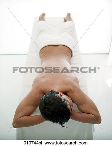Stock Photo of man with naked body lying on massage bench 010744bl.