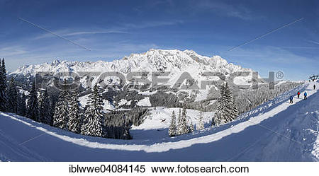 Stock Image of Skiers on ski slope in front of mountain scenery.