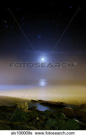 Stock Images of Moonset over the sea with Pleiades (M45) cluster.