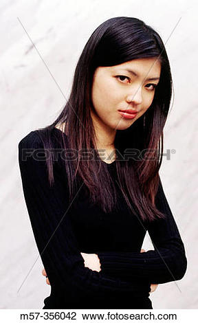 Stock Photo of Young long haired slim Asian female in a black top.