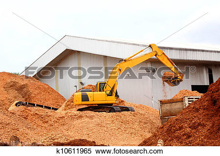Stock Image of Mulch Wood Pieces for make wood pulp with backhoe.