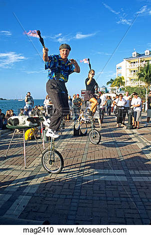 Stock Photography of couple entertainers jugglers on unicycles.