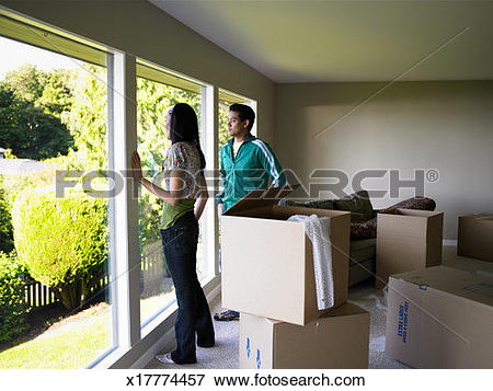 Picture of Young man and woman looking out window beside stack of.