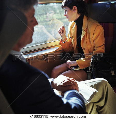 Stock Image of Man and woman riding train, woman looking out.