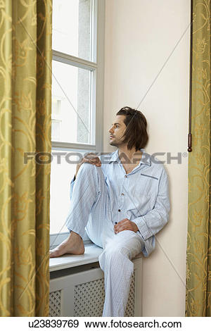 Stock Photograph of young man sitting on window sill wearing.