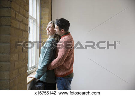 Stock Photo of Man stands behind woman, looking out of window.