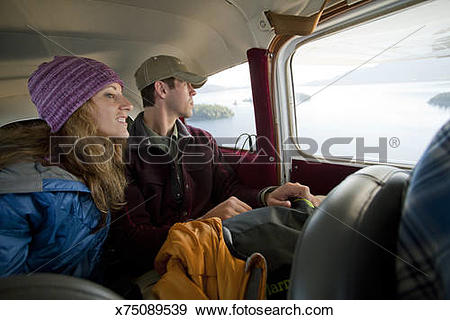 Stock Photograph of Woman and man looking out window of Cessna 185.