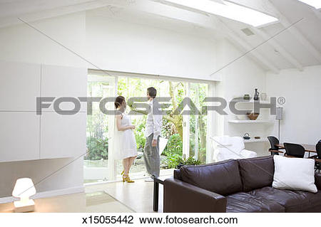 Stock Photo of Man and Woman looking out window in living room.