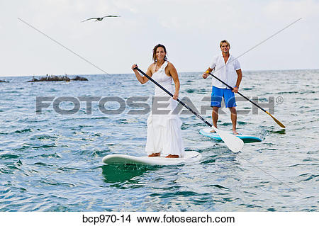 Stock Photo of Dressed up man and woman riding paddle boards.