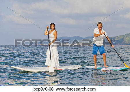 Pictures of Dressed up man and woman riding paddle boards bcp970.