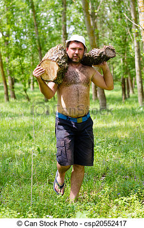Stock Photography of Strong muscular man carrying a large log of.