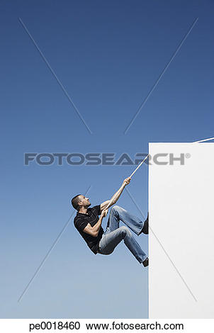 Stock Photography of Man climbing wall with rope outdoors with.