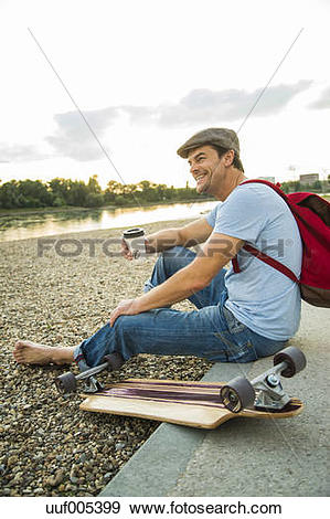 Stock Photograph of Smiling man sitting on stony beach with.