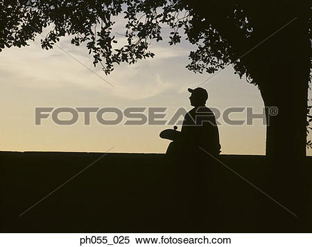 Stock Image of Silhouette of a young man sitting holding.