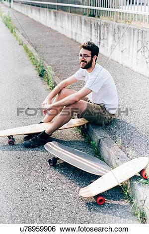 Stock Images of Young man sitting on kerb with three skateboards.